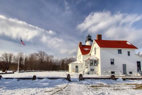 This is a photograph of Port Iroquois Lighthouse located in Hiawatha National Forest during the winter and covered in snow.