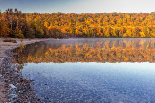 This is a photograph of Hiawatha National Forest in autum as the leaves change to beautiful orange and red colors overlooking a blue lake.