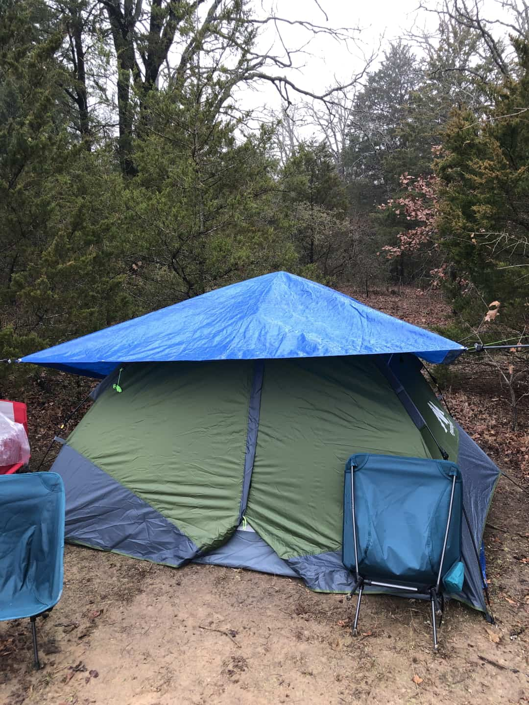 A pop-tent with an additional tarp tied over the tent to prevent rain from hitting the tent