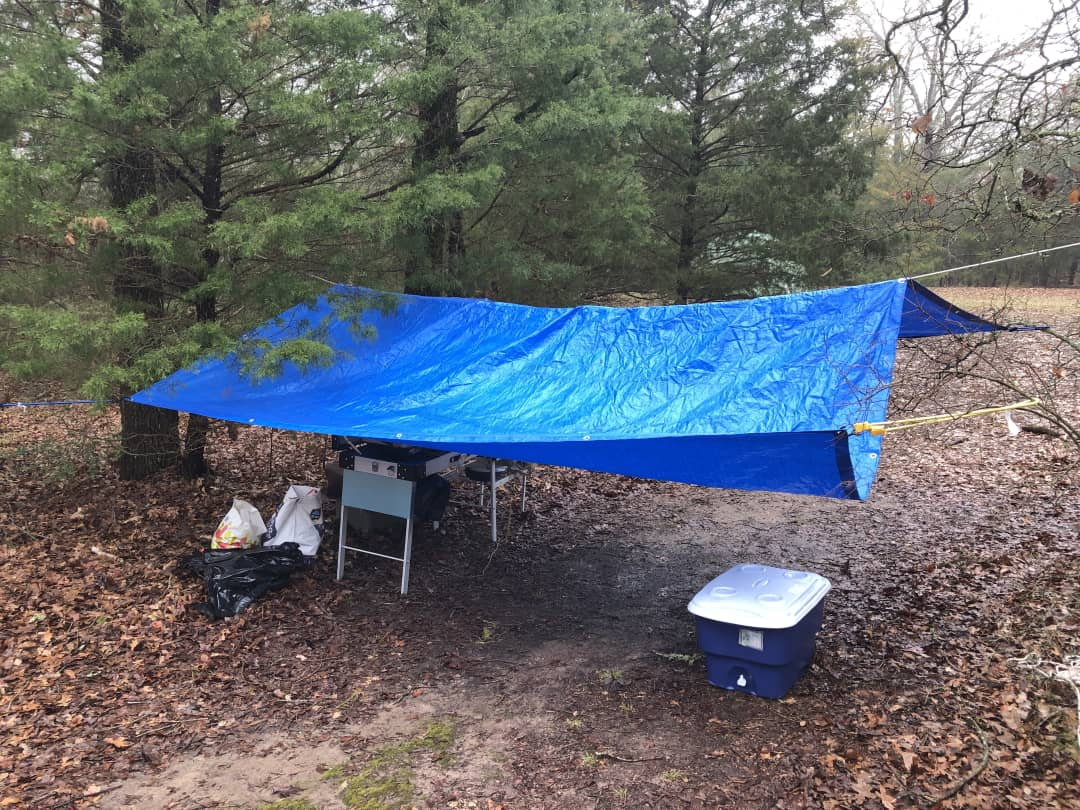 A tarp tied to a set of trees to keep a camp kitchen area dry in a rain storm.