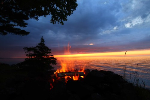 What You Should Pack and Cook On Your Weekend Camping Trip - Campfire by a lake at sunset